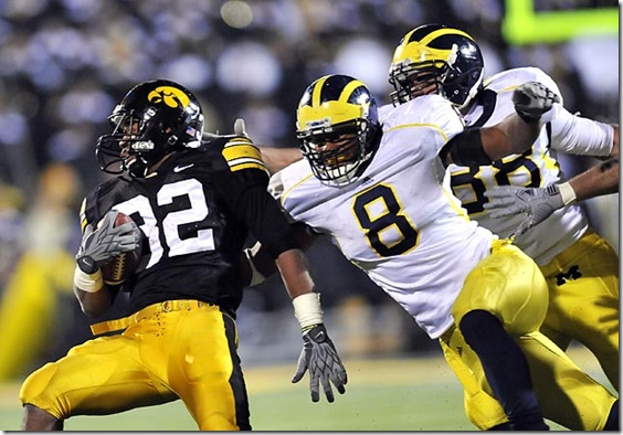 (caption) Michigan linebacker Jonas Mouton (8) and linebacker Craig Roh (far right) tackle Iowa running back Adam Robinson (32). Robinson rushed for 70 yards on 10 carries. *** Despite a late touchdown drive engineered by backup freshman QB Denard Robinson, the Michigan Wolverines came up short, losing to the unbeaten Iowa Hawkeyes 30-28 at Kinnick Stadium in Iowa City, Iowa. Photos taken on Saturday, October 10, 2009.  ( John T. Greilick / The Detroit News )