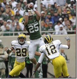 (CAPTION INFORMATION)Michigan State's Blair White leaps high for a first quarter reception over the top of Michigan's Troy Woolfolk, left, and J.T. Floyd.      Photos are of Michigan State University vs. the University of Michigan at Spartan Stadium in East Lansing, October 3, 2009.   (The Detroit News / David Guralnick)