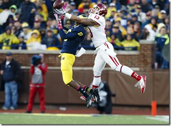 Oct 19, 2013; Ann Arbor, MI, USA; Indiana Hoosiers wide receiver Kofi Hughes (13) makes a touchdown catch over Michigan Wolverines defensive back Channing Stribling (8) in the third quarter at Michigan Stadium. (Rick Osentoski-USA TODAY Sports)
