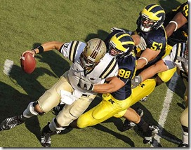 (caption) Michigan linebacker Craig Roh (88) and defensive tackle Ryan Van Bergen (53) get to Western Michigan quarterback Tim Hiller (3) for a sack. Michigan's Brandon Graham (upper right) was also in on the play. The Wolverines defense sacked Hiller twice in the game.  *** Michigan built a 31-0 first half lead, then coasted to a 31-7 season opening victory over Western Michigan University at Michigan Stadium in Ann Arbor. True freshman quarterback Tate Forcier threw three touchdown passes to lead the Wolverines.   ***  The University of Michigan Wolverines open Rich Rodriguez' second season against the Western Michigan University Broncos at Michigan Stadium in Ann Arbor. Photos taken on Saturday, September 5, 2009. ( John T. Greilick / The Detroit News )