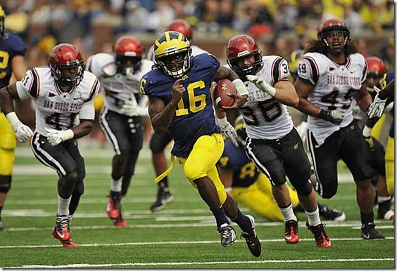 (caption) Michigan quarterback Denard Robinson breaks away from the San Diego State defense for a big gain in the second quarter. Robinson rushed for 200 yards and three touchdowns on 21 carries, a 9.5-yards-per-carry average. He struggled in the passing game, however, completing just 8 of 17 passes for 93 yards with two interceptions.  *** After jumping out to a 21-0 lead by halftime, courtesy of three rushing touchdowns by Michigan quarterback Denard Robinson, the Wolverines turned the ball over three times in the second half, but held on to beat coach Brady Hoke's former team, the San Diego State Aztecs 28-7 at Michigan Stadium in Ann Arbor. Photos taken on Saturday, September 24, 2011. ( John T. Greilick / The Detroit News )