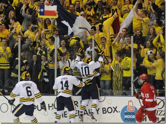 Michigan junior Chris Brown jumps up on the glass to cheering fans after scoring the first goal of the game, on the day of his birthday. Fans waved signs and Texas flags to celebrate his birthday. Angela J. Cesere | AnnArbor.com