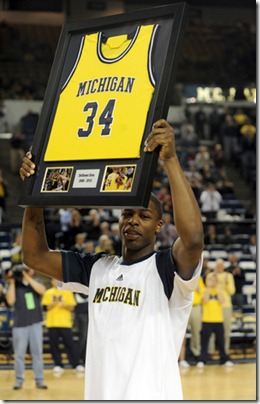 Michigan's DeShawn Sims holds up a framed game jersey as he and fellow seniors Zack Gibson and Anthony Wright were recognized before their final game at Crisler Arena. The seniors went out winners with a 83-55 trouncing of Minnesota, Tuesday night March 2nd. 