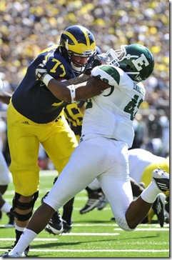 (caption) Michigan OL Taylor Lewan (77) blocks Eastern Michigan Eagles linebacker Marcus English (42), paving the way for Denard Robinson's rushing touchdown  in the second quarter.    *** The Michigan Wolverines (2-0) host the Eastern Michigan Eagles (2-0) at Michigan Stadium in Ann Arbor. Photos taken on Saturday, September 17, 2011. ( John T. Greilick / The Detroit News )