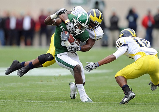 Michigan's Obi Ezeh, top, and J.T. Floyd, right, team up to bring down  Michigan State University wide receiver Mark Dell after a short gain during first quarter action of Saturday afternoon, October 3rd's clash between the in-state rivals at Spartan Stadium in East Lansing.<br /> Lon Horwedel | AnnArbor.com