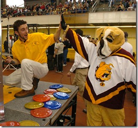 Jason Cook, a member of Ferris State University's Rube Goldberg team the Underdogs, pauses from his work to give a high-five to Ferris State's mascot, Brutus the bulldog. The Underdogs, from Big Rapids, Mich., finished second today (Saturday, 4/3) in the National Rube Goldberg Machine Contest at Lambert Fieldhouse. (Purdue News Service photo/Dave Umberger)rubenat04-ferris.jpg