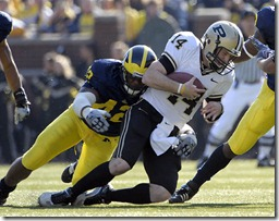 (CAPTION INFORMATION)<br /> Purdue's Joey Elliott is sacked by Michigan's Al Backey in the first quarter.         Photos are of the University of Michigan vs. Purdue University at Michigan Stadium, November 7, 2009.    (The Detroit News / David Guralnick)<br />